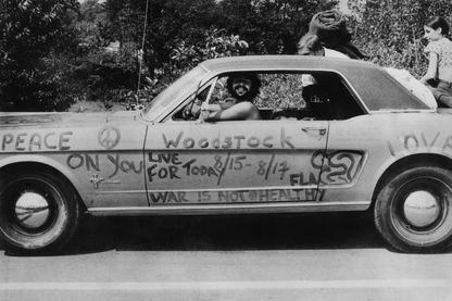 Un fan de musique au festival pop de Woodstock dans sa voiture, couvert de slogans anti-guerre pour l'amour et la paix.