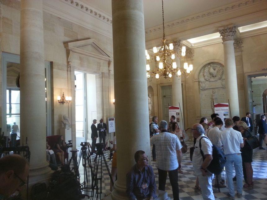 La salle des quatre colonnes, envahie de journalistes.