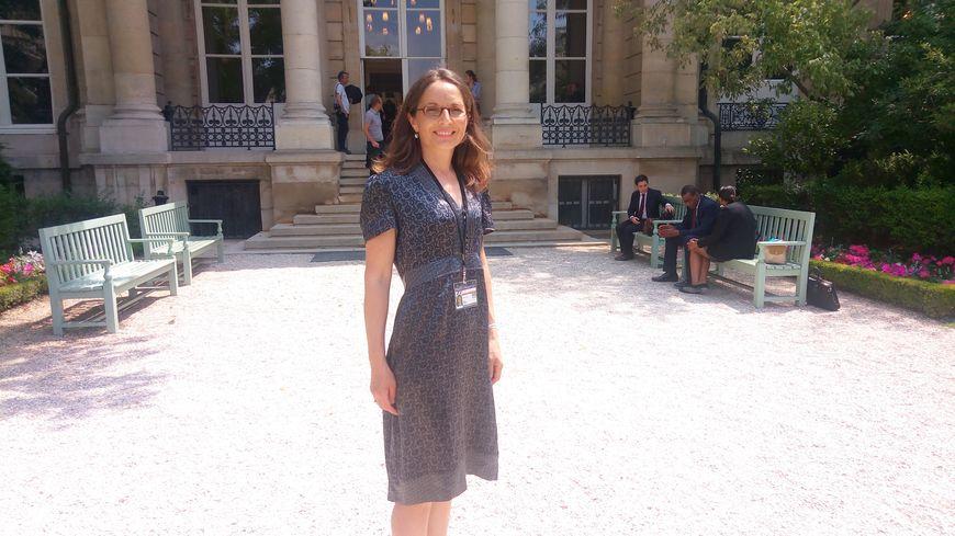 Liliane Tanguy pose devant l'Assemblée avec son badge de députée