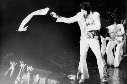 Elvis lance l'une de ses fameuses écharpes de soie dans le public...