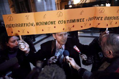 Protestation d'un homme avec une affiche pendant le procès du scandale des hormones de croissance au Palais de Justice de Paris le 14 janvier 2009.