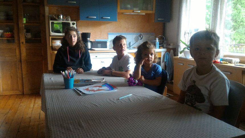 Quatre enfants, quatre tailles différentes, et tous assis à hauteur de table, sur la même chaise.