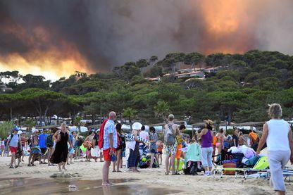 Des vacanciers quittent la plage avec leurs biens en regardant le feu qui brûle une forêt derrière eux à Bormes-les-Mimosas, dans le sud-est de la France, le 26 juillet 2017.