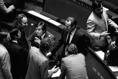 Des députés félicitent le ministre de la Justice Robert Badinter (C) dans l'hémicycle de l'Assemblée nationale, le 17 septembre 1981 à Paris, après l'examen de son projet de loi sur l'abolition de la peine de mort.