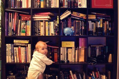 Un bébé debout contre une étagère de bibliothèque à la maison