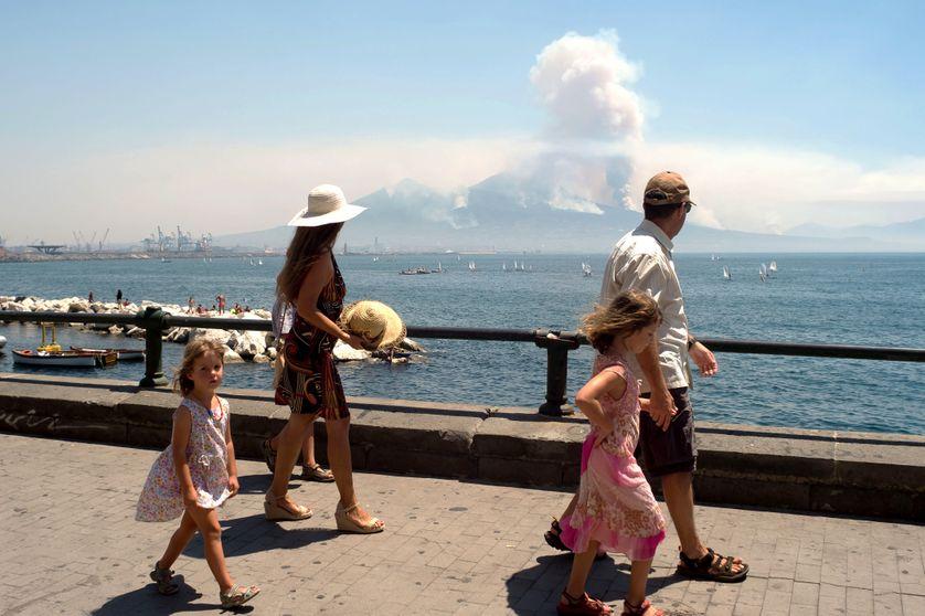 Sur la promenade de Naples, des passants regardent au loin la fumée s'échapper du Vésuve