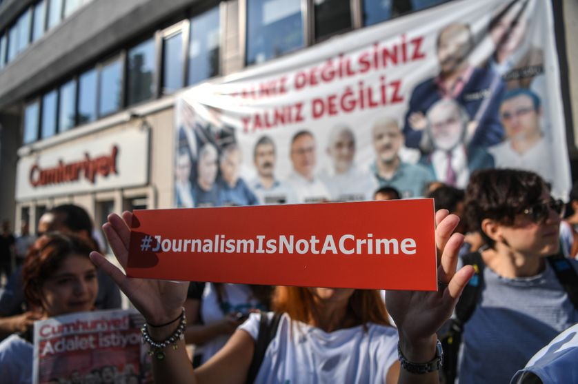 A journalist holds a banner on July 24, 2017 outside the headquarters of opposition daily newspaper Cumhuriyet in Istanbul.