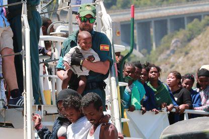 Un officier de la Guardia Civil aide les migrants à débarquer du navire espagnol Rio Segura dans le port de Salerne, Italie - 29 juin 2017