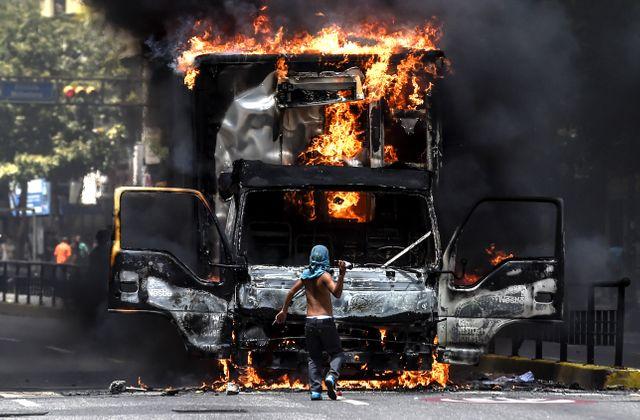 Un opposant à Maduro face à un camion en feu dans les rues de Caracas, 18 juillet 2017