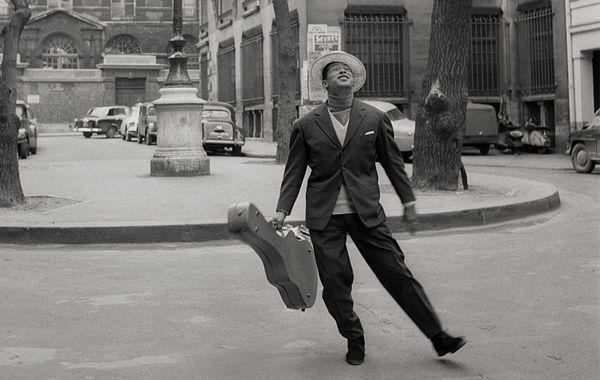 Henri Salvador dans les rues de Paris, étui de guitare à la main.