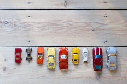 Voitures jouet alignées dans une rangée sur le sol.