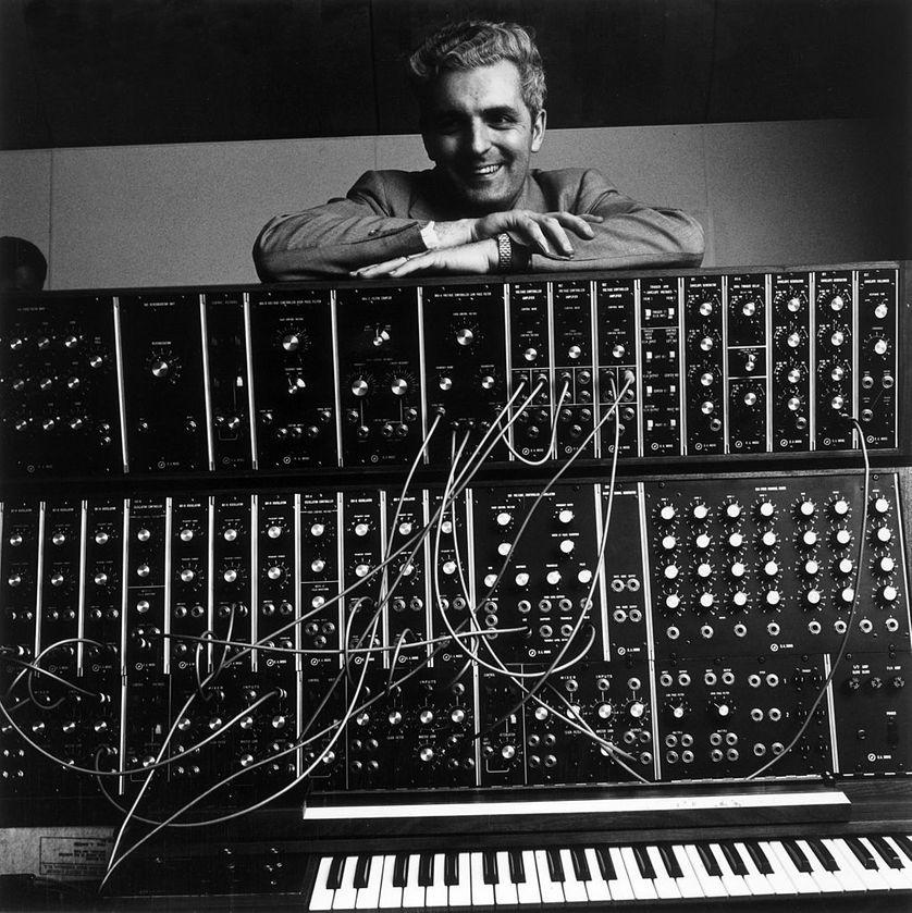 Janvier 1970 : Portrait de l'inventeur Robert Moog, souriant et les bras croisés sur son synthétiseur Moog