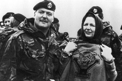 La première ministre britannique Margaret Thatcher pose avec un soldat du 1er bataillon du Royal Hampshire et affiche un Tee-Shirt portant l'emblème de ce régiment, pendant l'offensive sur les Malouines pour les récupérer, en 1982.