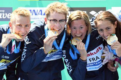 L'équipe de France Marc-Antoine Olivier, Logan Fontaine, Aurélie Muller et Océane Cassignol célèbrent leur victoire sur le podium après avoir remporté l'épreuve mixte de natation à eau libre reliée à l'équipe de 5 km le 20 juillet 2017.