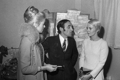 Le chanteur français d'origine arménienne, Charles Aznavour (C) discute avec les actrices française Catherine Deneuve (G) et américaine Jean Seberg, le 19 janvier 1968 à Paris, après son concert à l'Olympia.