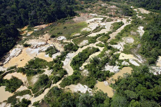 Vue aérienne d'une partie d'un site d'exploitation aurifère clandestin, le long d'un affluent du fleuve Maroni en pleine forêt guyanaise.