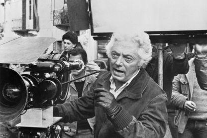 Le cinéaste Dino Risi apparaît derrière une caméra de cinéma, lors du tournage de l'un de ses films (lieu et date inconnus)