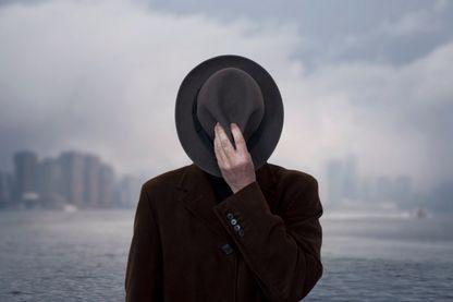 Portrait d'un homme avec le visage couvert par un chapeau.