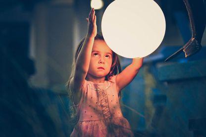 Petite fille qui regarde et joue avec une lune.