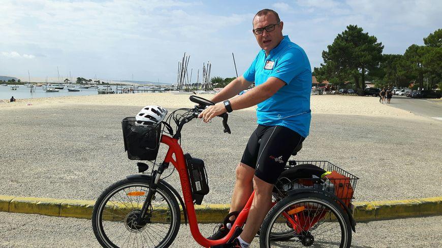Philippe Meynard sur son tricycle au Cap Ferret