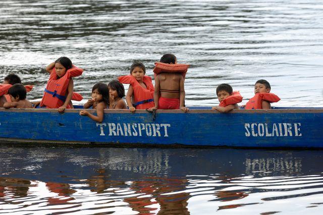 Des enfants de la tribu Wayana, du village de Twenke qui vont à l'école dans une barque, sur la rivière Maroni.