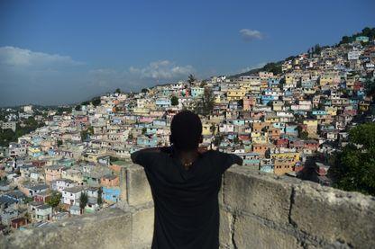 Un garçon regarde les maisons sur la montagne dans le quartier de Jalousie à Port-au-Prince - 16 aout 2017