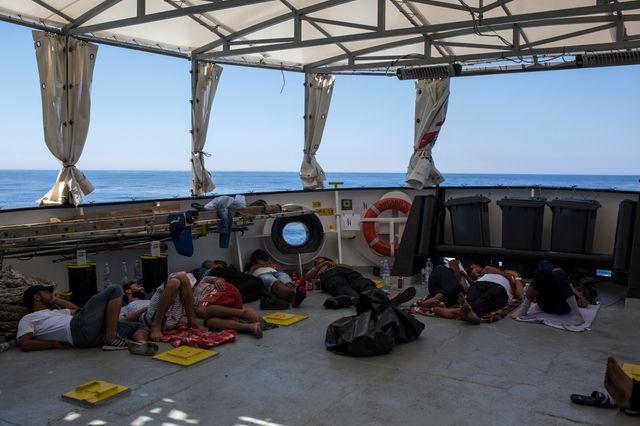 Des migrants libyens dorment sur le pont de l'Aquarius après leur sauvetage en Méditerranée, à 20 milles nautiques de la côte libyenne, le 2 août 2017.
