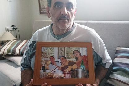 Gil Grunbaum tient dans ses mains une photo où l'on voit son fils avec ses cousins : sa famille biologique qu'il a retrouvée.