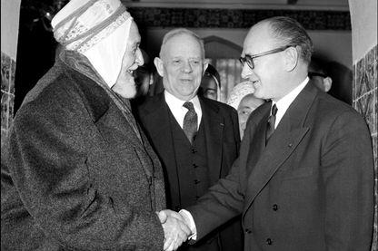 Le Président du Conseil, Guy Mollet (D), serre la main du Président de l'Assemblée algérienne Salah Abd el Kader le 08 février 1956, lors de sa visite à Alger.