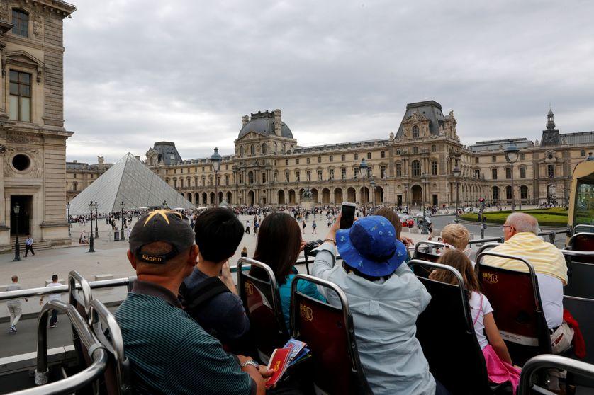 Des touristes à bord d'un bus à étage photographient leur arrivée tout près du musée du Louvre à Paris.
