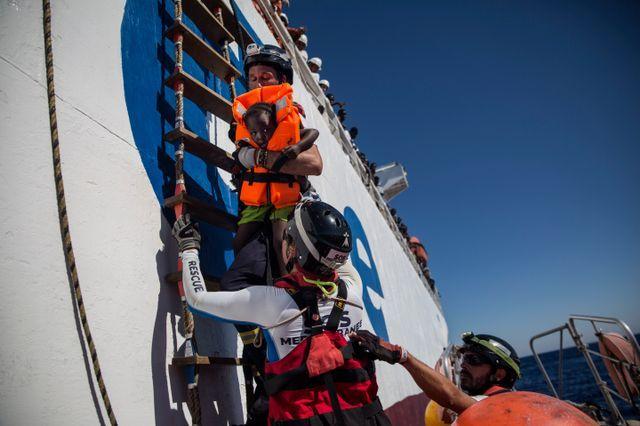 Un sauveteur de l'Aquarius tient une petite fille récupérée avec d'autres personnes depuis le navire marchand Santa Lucia en Méditerranée, à 20 milles nautiques de la côte libyenne. / AFP