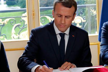 Le président français, Emmanuel Macron, signe des documents devant les médias pour promulguer une nouvelle loi sur le travail dans son bureau à l'Elysée à Paris, le 22 septembre 2017.