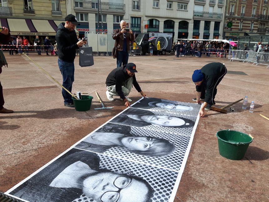 Tout juste sorties du photomaton de JR, les affiches sont collées au sol, sur l'Esplanade de l'Hotel de Ville