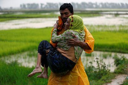 Un homme porte une vieille femme réfugiée Rohingya car elle est incapable de marcher après avoir traversé la frontière, à Teknaf, au Bangladesh.