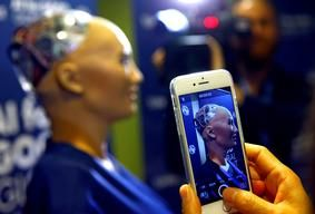 """Geneva, Switzerland An attendee takes a picture of Sophia, a robot integrating the latest technologies and artificial intelligence created by Hanson Robotics, during a presentation at the """"AI for Good"""" Global Summit at the International"""