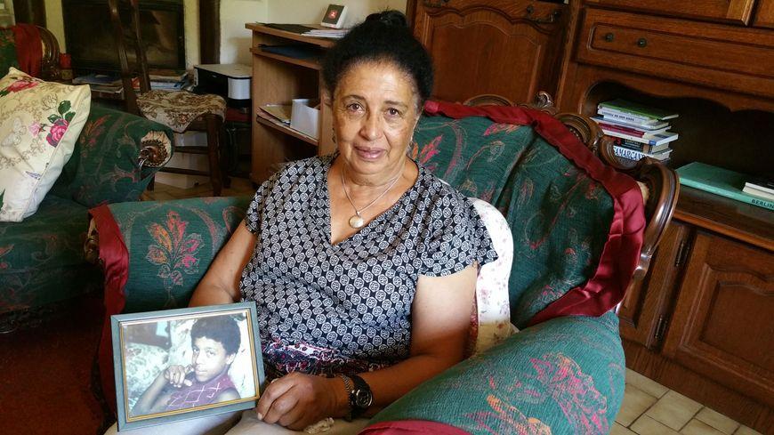 Aïcha El-Wafi avec la photo de Zacarias, assise sur le fauteuil préféré de son fils.