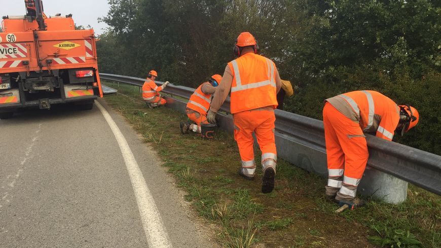 Des ouvriers installent un écran motos sous une glissière de sécurité sur une route départementale à Saligny (Vendée)
