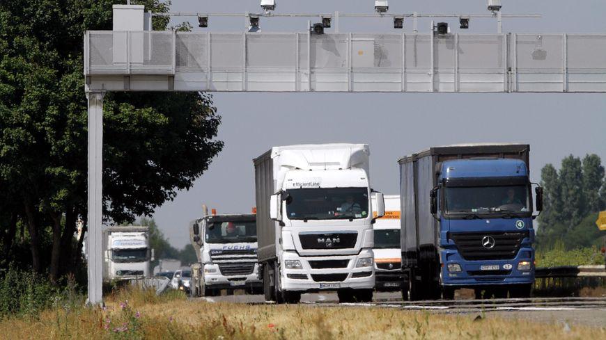 Des camions passent sous un portique de péage de transit (illustration)
