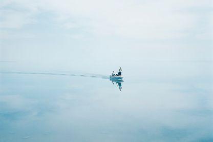 Etendue d'eau, une barque au loin avec des personnes à bord, photo illustrant la pochette de disque du Chris Tordini Trio
