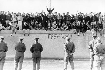 Pendant la chute du mur de Berlin avec des gens sur le mur et devant eux les Vopos (gardes-frontières) le 10 novembre 1989