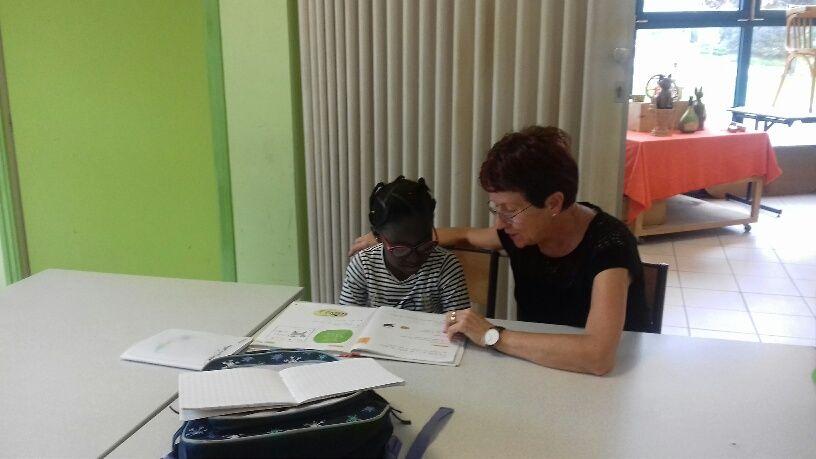 Odette aide Bahabo en CP à faire ses devoirs