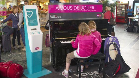 Des usagers de la SNCF jouent sur l'un des 100 pianos en libre service dans les gares françaises