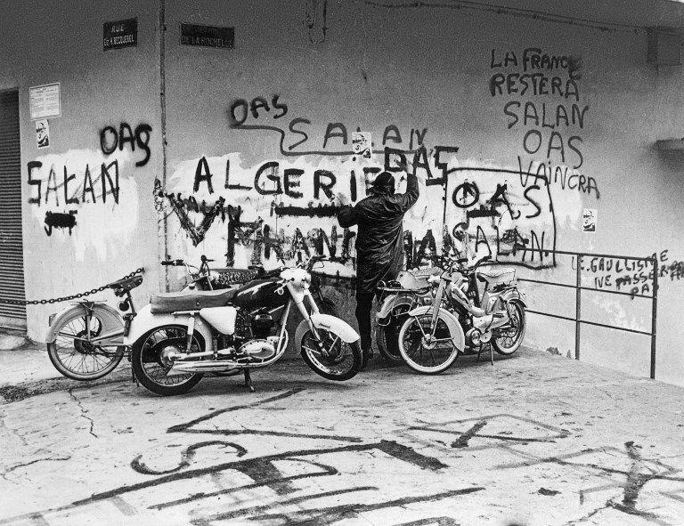 Photo prise le 04 mars 1962, pendant pendant la guerre d'Algérie, d'un homme lisant des graffitis en faveur de l'OAS, l'organisation de l'armée secrète prônant l'Algérie française, sur un mur d'une rue d'Alger.