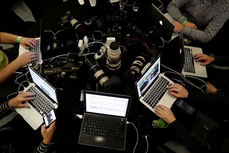 Photographers work on computers at an election headquarters of ANO party in Prague, Czech Republic October 21, 2017.