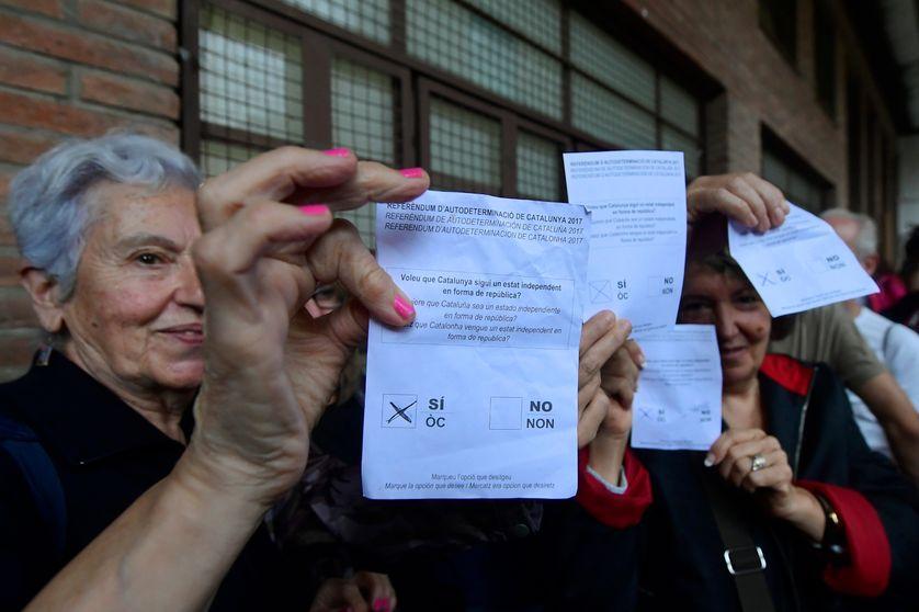 Des catalans avec leur bulletin de vote pour le référendum d'autodétermination du 1er octobre