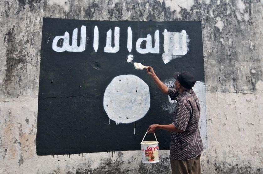 Un fonctionnaire indonésien efface les drapeaux de l'Etat islamique peints sur les murs de la ville de Surakarta (Java).