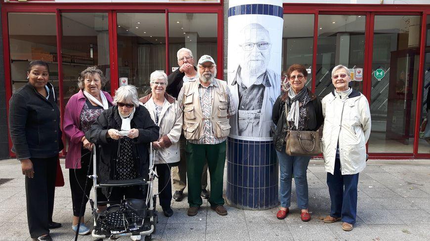 Les modèles posent autour d'un des portraits, place du Caquet,  Saint-Denis