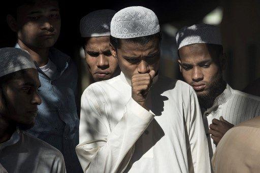 Des Bangladais, choqués après la découverte de cadavres de Rohingyas qui ont fait naufrage