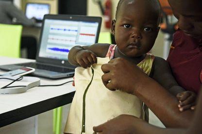 Olivia Kaburongo essaie sur un bébé la veste MamaOpe
