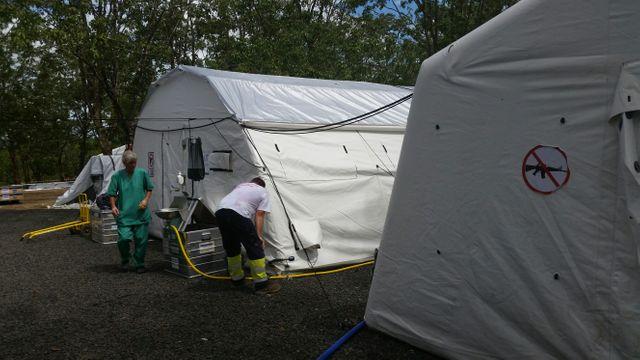 """""""L'hôpital de terrain de la Croix Rouge, en bordure des camps. A l'entrée des tentes où se reposent ou sont opérés des patients, un panneau interdit les armes"""""""